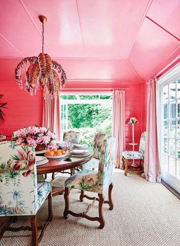 a pink dining room in the home of interior designer Charlotte Coote, featuring a tropical-inspired chandelier and upholstery