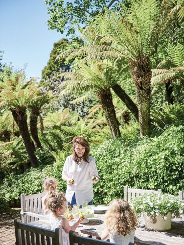 Australian designer Charlotte Coote with her 3 young daughters at the table on an outdoor dining terrace