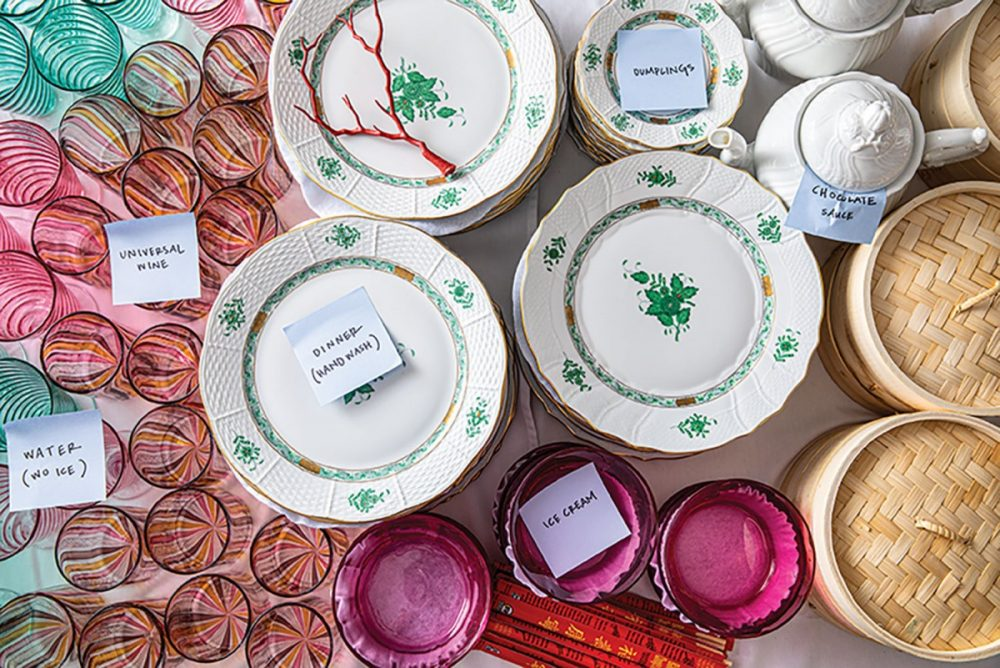 A table full of colorful glassware, white and green dinnerware, and serveware--including steamer baskets, white teapots, and chopsticks--set out and labeled for Rebecca Gardner's chinoiserie-themed party