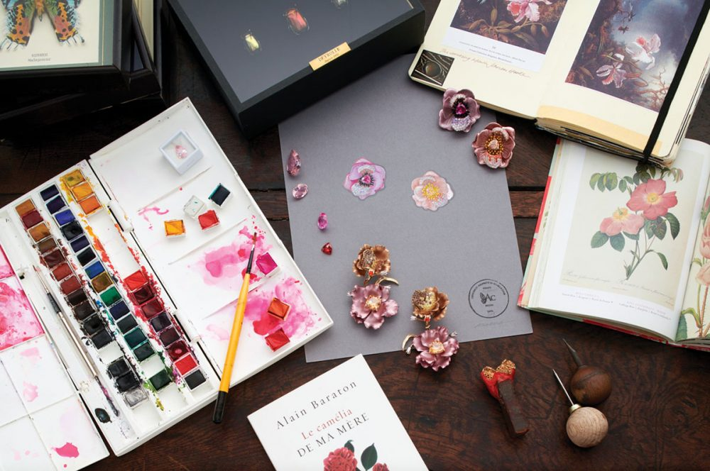 earrings by Anabela Chan on a desk with inspirational books, paints, and paintbrushes