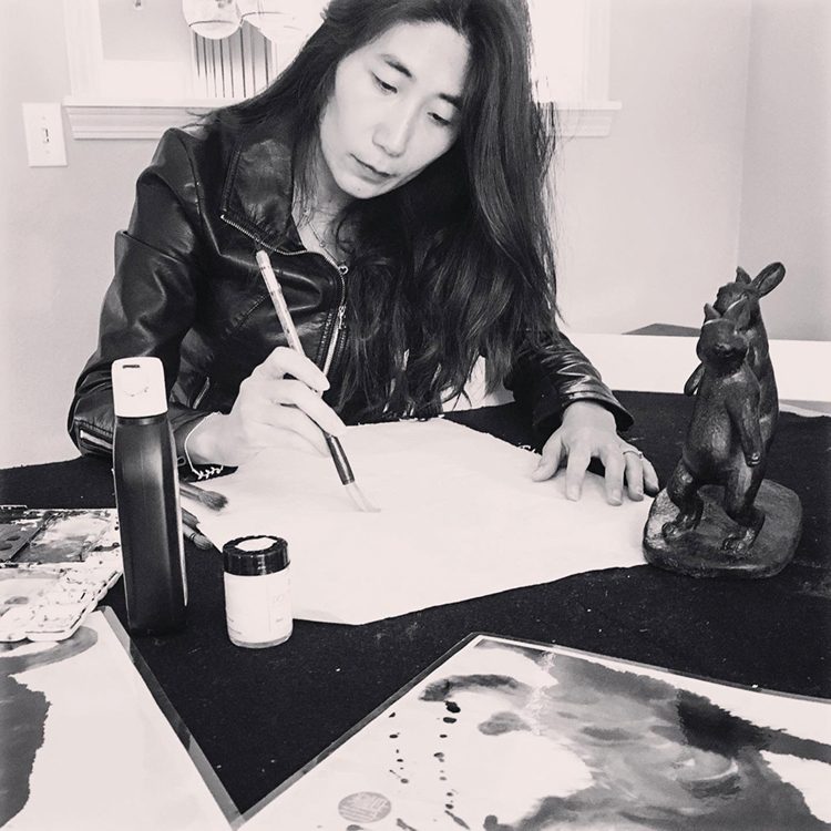 black-and-white portrait of artist Anita Wong, wearing a black leather jacket, drawing her paintbrush across paper
