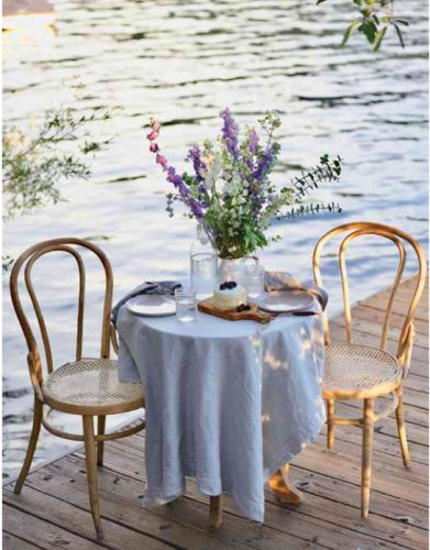A cafe table and chairs, with blue tablecloth and flowers, on a dock by the water.
