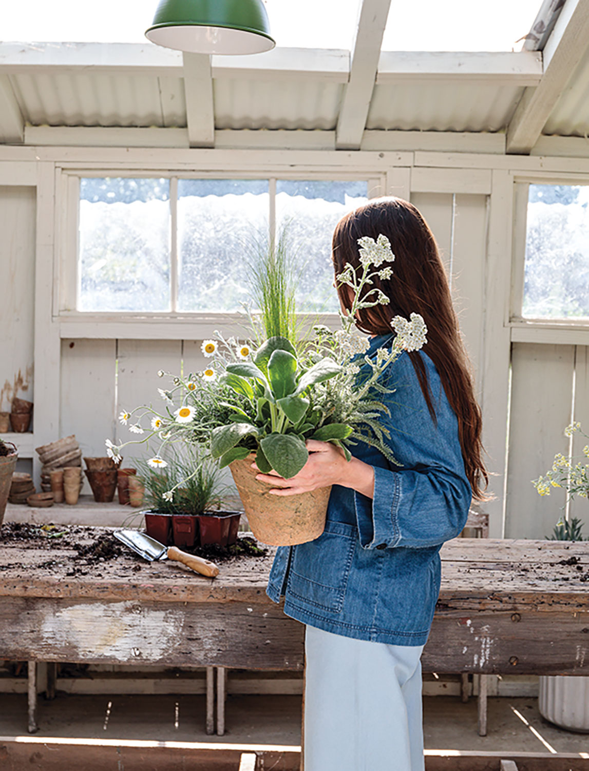 Kristen Caissie stands in a white, light filled potting shed, holding a centerpiece arrangement of potted plants
