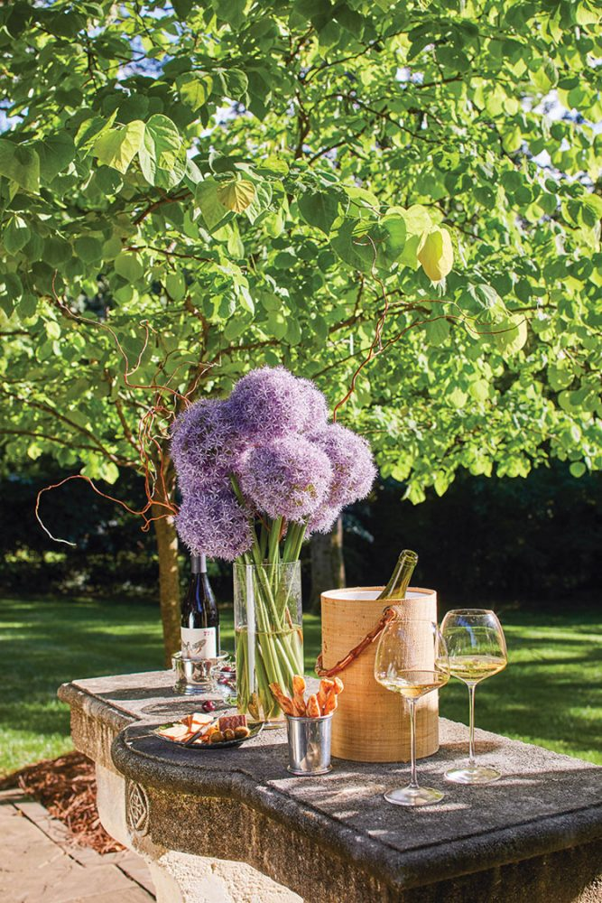 a vase of purple allium blooms wine, and appetizers on a stone outdoor table
