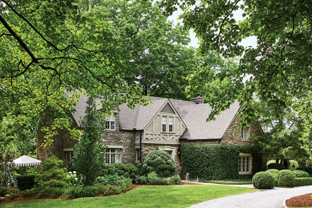 English Tudor exterior of landscape architect Gavin Duke's home, surrounded by lush trees, lawn, and landscaping