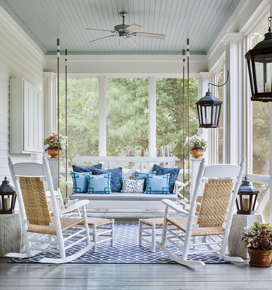 Photo the screened porch at McCurdy Plantation. Designer James Farmer chose a gray floor and light blue ceiling, and furnished it with two rocking chairs and a bed swing covered in blue pillows.