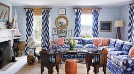 A blue-and-white living room featuring bold patterns and deep coral accents