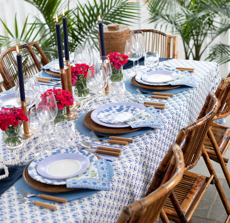 Caspari blue and white table with palm fronds and hot pink flowers