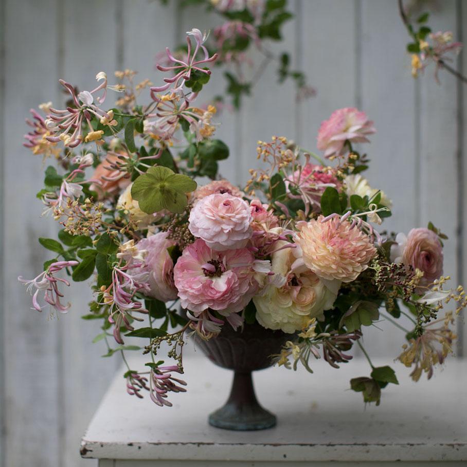 Pink and coral spring floral arrangement with Snowberry 'Hancock', Blueberry 'Duke' foliage, Honeysuckle 'Munster', Helleborus orientalis, Ranunculus Pastel Mix, Heuchera 'Amber Waves', Filipendula ulmaria