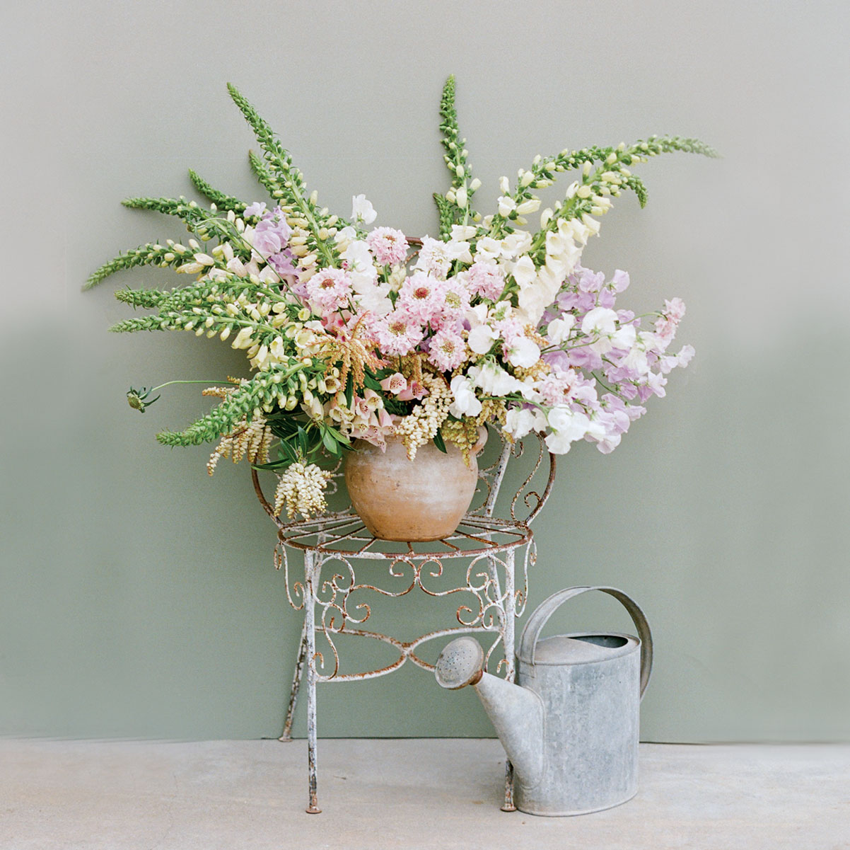 large summer floral arrangement with pastel pinks, purples, white and green, designed by Kate Holt in a clay vessel, displayed on an antique metal garden chair beside a metal watering can, against a pale gray-green wall