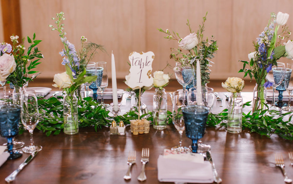 wedding table featuring flowers in small bottles scattered down the table, along with a runner of loose greenery