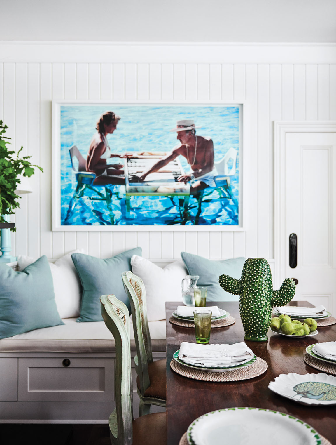 Above a banquette, the Slim Aarons' photograph features couple playing a board game in a pool