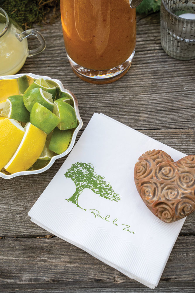 A stack of cocktail napkins bearing a tree motif and the name Rancho La Zaca beside a silver dish of sliced lemons and limes