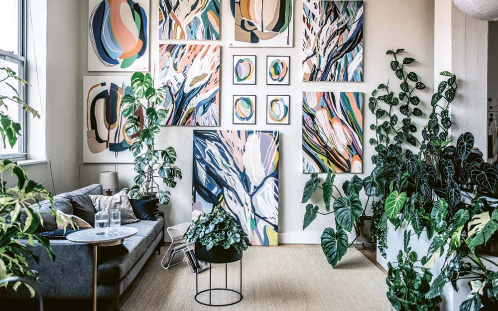 A scene from the houseplant-filled apartment and studio of Brooklyn artist Alina Fassakhova. Her colorful, abstract botanical paintings fill the back wall. A charcoal-colored modern sofa sits under a window on the adjacent wall. The sofa faces a wall of lush, green plants; individual plants accent other areas of the room.