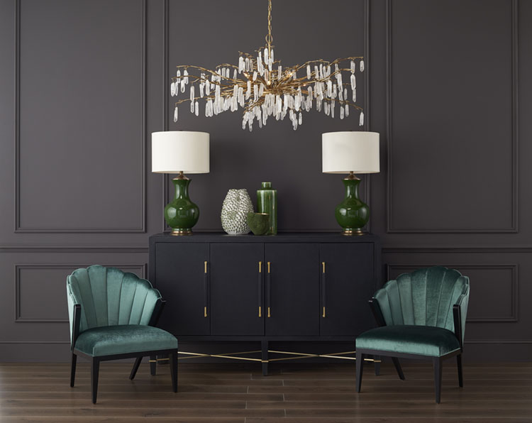 A botanically inspired chandelier design from Curry & Company, which features natural quartz crystals hanging from golden spokes that resemble branches of a tree, hangs in an elegant room painted charcoal gray. A pair of emerald green table lamps and vases stand on a sideboard with a black finish, which is flanked by a pair of curvy, green velvet side chairs.