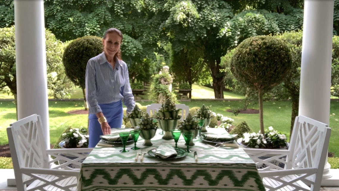 Carolyne Roehm stands beside an outdoor table set with green and white, with a view of a her formal garden behind her