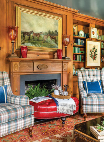 two plaid wing chairs flank a tufted red leather oval ottoman and a fireplace in a pine-walled study designed by James Farmer