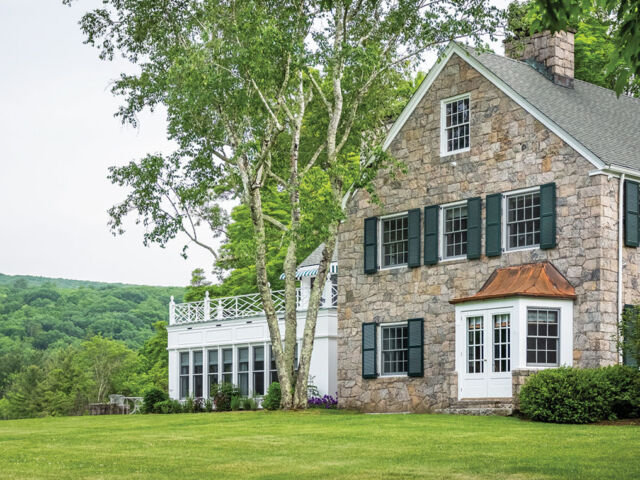 stone 2-story home with copper-roof bay window and large attached 1-story sunroom with a patio on the roof.