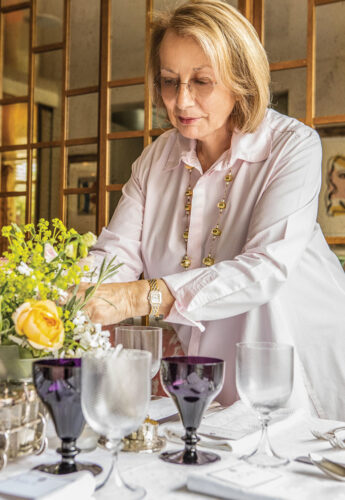 Nina Campbell sets the table wearing a long, stylish white blouse and long necklace