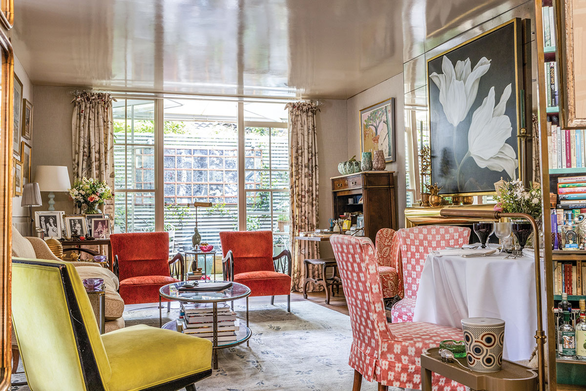 Nina Campbell's London drawing room, featuring neutral walls, a lacquered ceiling, cheerfully colored upholstery, and a large floral painting above the mantel