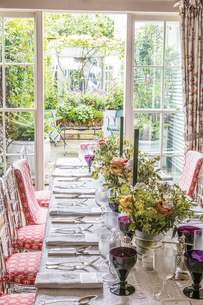 A flower-filled table setting in Nina Campbell's dining room. The french doors are open, leading to the garden terrace beyond