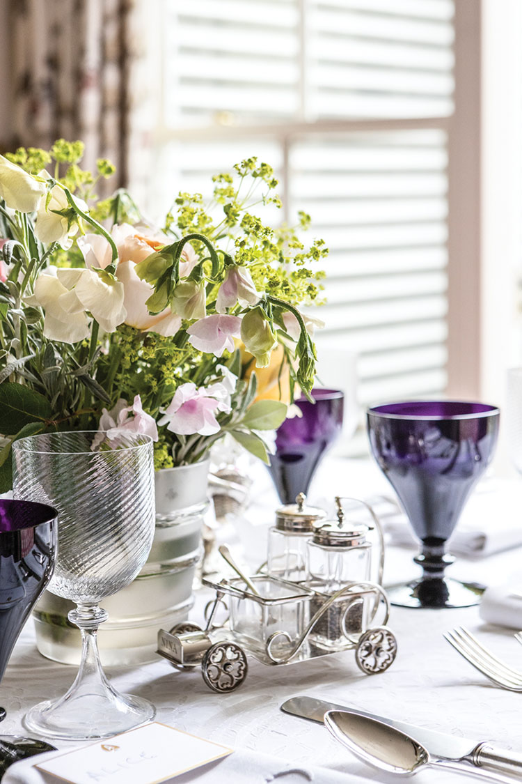 William Yeoward's amethyst goblets, salt and pepper set in a silver holder shaped like an antique car, and a garden-inspired centerpiece