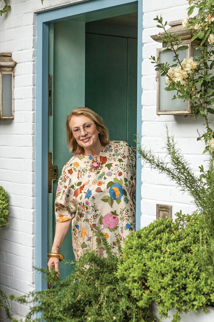 portrait of designer Nina Campbell standing in her front door. The brick of her home is painted white, and the door frame and room behind her are a muted blue