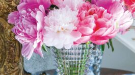 Pink peonies in Baccarat's Crystal Eye Vase. In the background stands an ornate gilt frame mirror