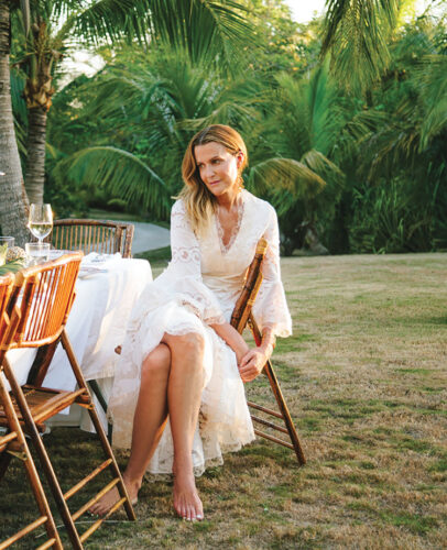 author of an Entertaining Story, India Hicks, wearing a white flower dress, sitting at an outdoor table with palm trees in the background