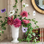 Loose, garden inspired arrangement of dark pink dahlias, white and light purple anemones, and trailing vines by floral designer Mieke ten Have in a white pottery vase