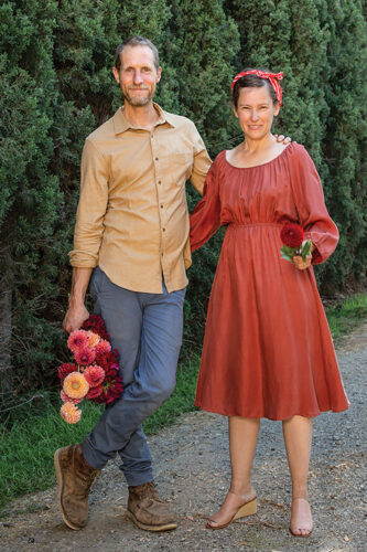 Ceramics artist Josh Beckman of FBP Works and floral designer Holly Vesecky stand on a gravel road bordered with an allee of evergreens. Josh wears a tan button up, jeans and hiking books, and holds a bouquet of dahlias by his side; his other arm is around Holly. He crosses one foot casually over his standing leg. Holly wears a rust colored Bohemian-style dress, a scarf around her head and tan wedge sandals. She holds a red dahlia in one hand.