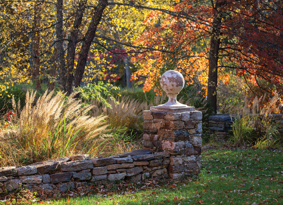 A low stone wall borders a bed of tall autumn grasses at Jardin de Buis in New Jersey. Sun shines through the red and yellow autumn foliage.