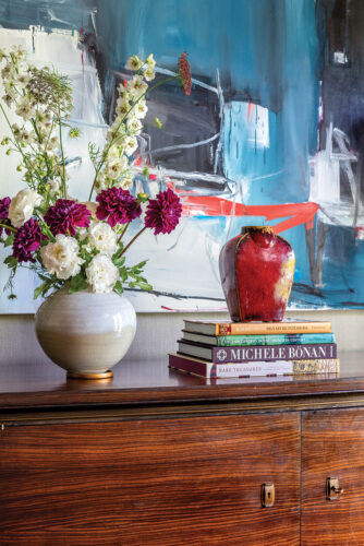 flowers, pottery vases, and a stack of books on a cleanl-lined wood sideboard. An abstract painting with blue tones and pop of red hangs in the background in a vignette by designer Matthew Patrick Smyth
