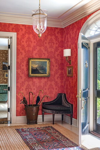 Red damask wallpapered entry hall with an oriental rug layered over a larger sea grass rug in a home designed by Matthew Patrick Smyth. A formal antique corner chair, traditional moldings, and gold framed antique paintings finish the space.