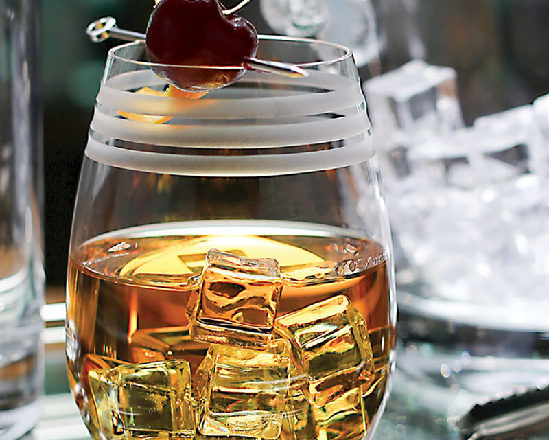 bourbon on the rocks in a crystal wine tumbler, garnished with a cherry on a pick
