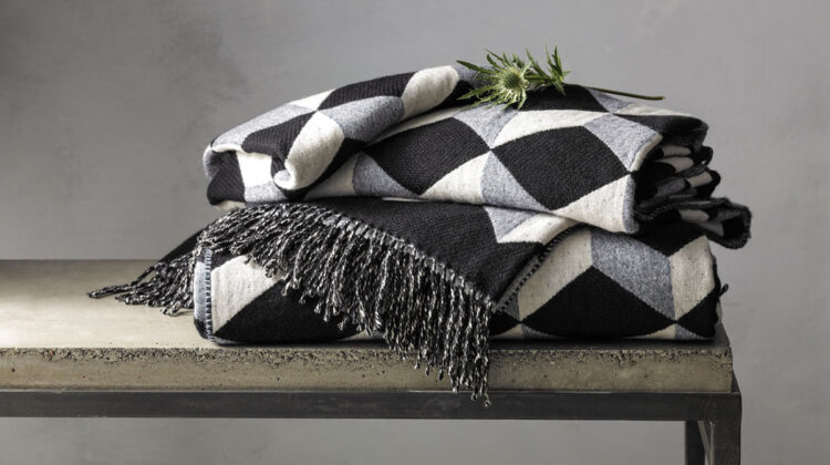 menswear-inspired wool and cashmere throw in a geometric patter of black, gray, and off-white, folded and placed on a bench