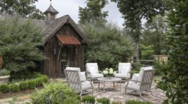 A set of 4 white-cushioned patio chairs, available through Blackjack Gardens in Birmingham AL, surround a small white table on a brick patio. The patio is surrounded by a lush green garden. The adjacent home is a rustic cabin with an aged metal overhang and a classic weathervane on roof.