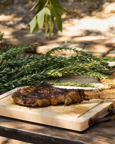 Seared bone-in rib-eye steak on a cutting board. A bundle of fresh rosemary lies beside it.