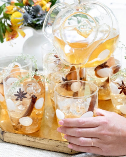 A glass pitcher and tumblers filled with a chilled cider, with cinnamon sticks and star anise, set on a wooden tray painted gold
