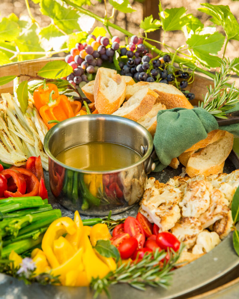 A silver dish of bagna cauda on a platter of sliced colorful sweet peppers, tomatoes, assorted breads for dipping, and grapes