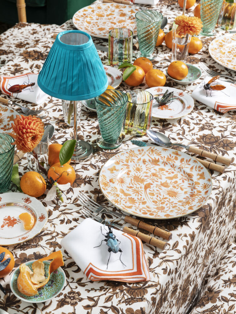 fall table featuring orange and brown botanical prints, accentuated with oranges, orange dahlias, and teal accessories