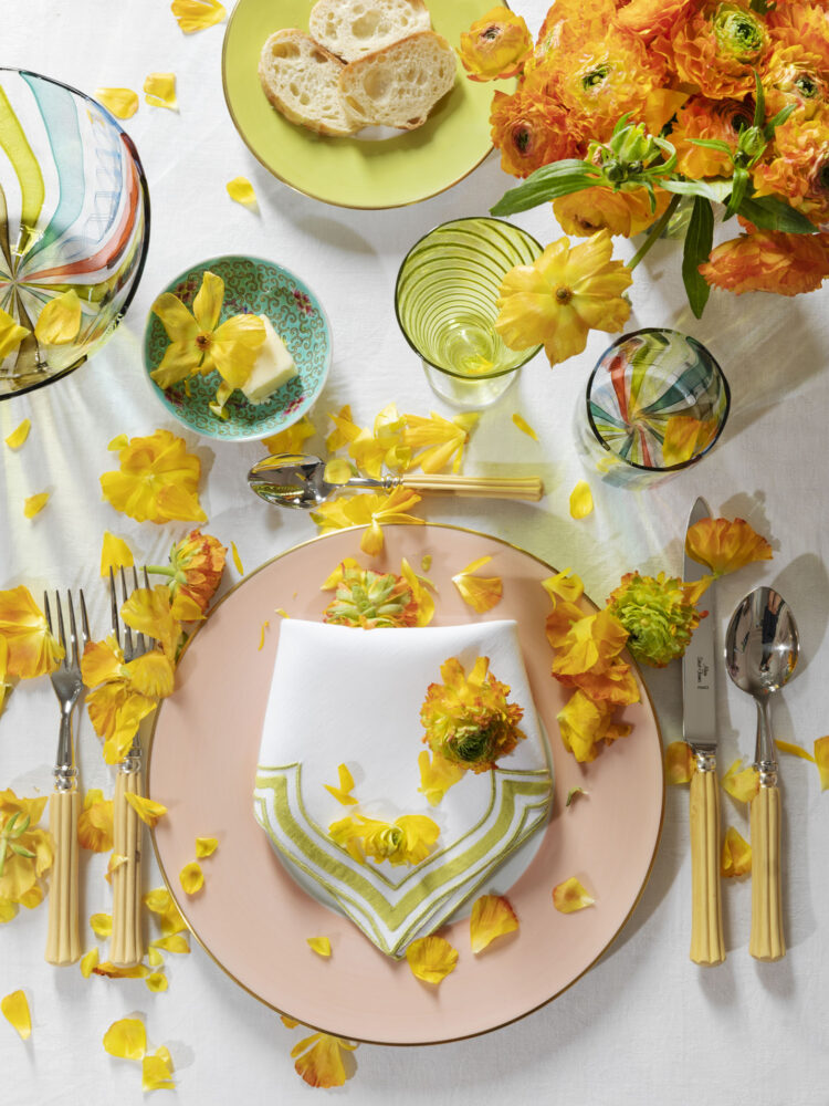 summer table from Rebecca Gardner's Houses & Parties featuring dinnerware in peach, green, and teal, with vibrant yellow and orange flowers