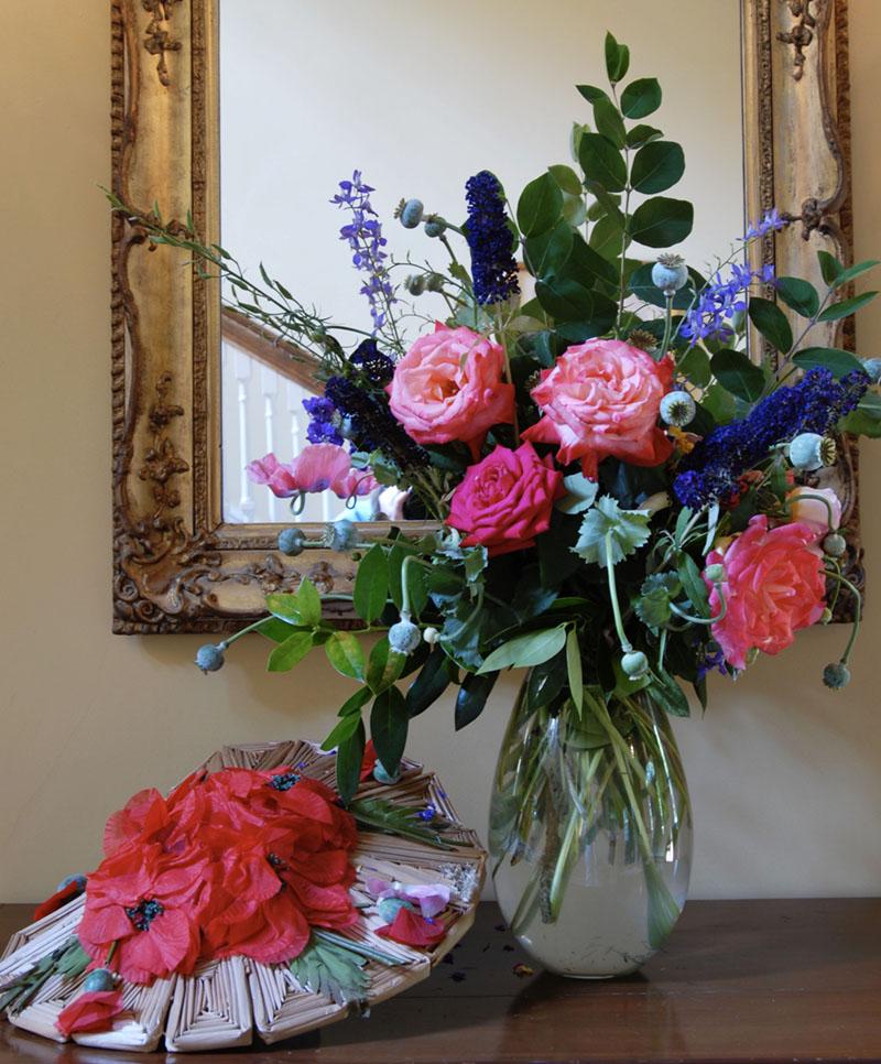vase of flowers, displayed in front of a gilt framed mirror, beside a vintage flower-bedecked hat