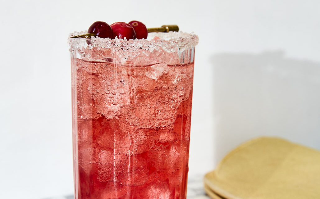 Highball glass filled with ice and Cranberry Shrub Cocktail from Very Merry Cocktails by Jessica Strand. The glass is rimmed in sugar and garnished with a skewer of cranberries. A gold clutch lays on the gray and white marble counter beside it.