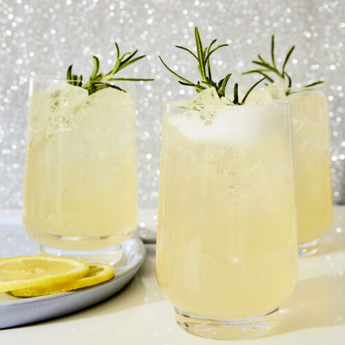Three glass tumblers filled with Evergreen Sparkler, a fizzy lemon, rosemary, and gin cocktail from the book Merry Cocktails by Jessica Strand. Rosemary sprigs garnish each glass. The background is a glittery silver.