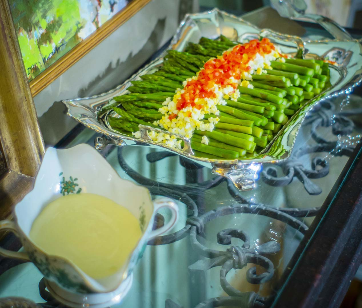 """Steamed asparagus in a Sterling Asparagus Tray by Tiffany & Co, with a side of hollandaise sauce in a Herend """"Indian Basket"""" Green gravy boat, both from Replacements Ltd"""