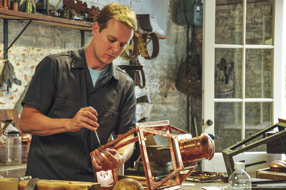 a craftsman at Bevolo works on a copper gas lantern