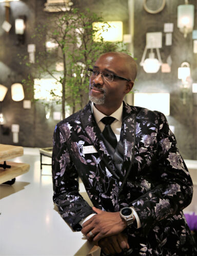 Currey and Company Senior Lighting Designer Ian Thornton, creator of the Multi Drop Pendant Collection, stands in the showroom wearing a dark floral print suit coat.