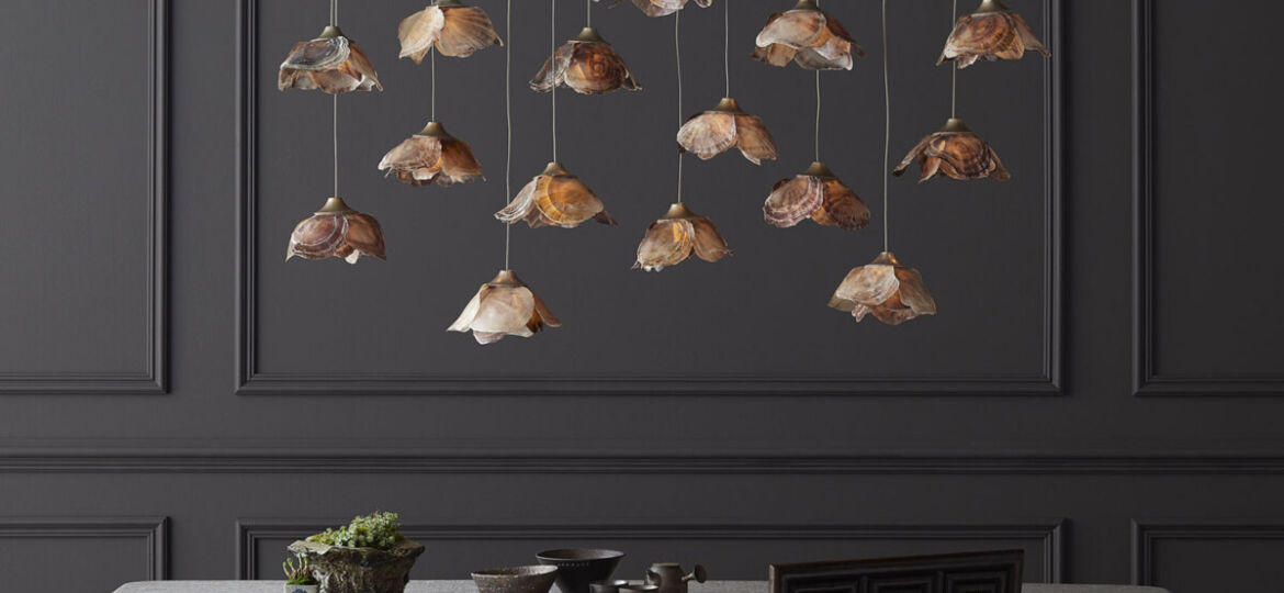A light fixture of 14-pendant lights, with flower-shaped shades made from shells, hangs over a dining room table against a backdrop of wainscoting painted charcoal gray. The fixture is part of Currey and Company's new Made to Measure Pendant Collection