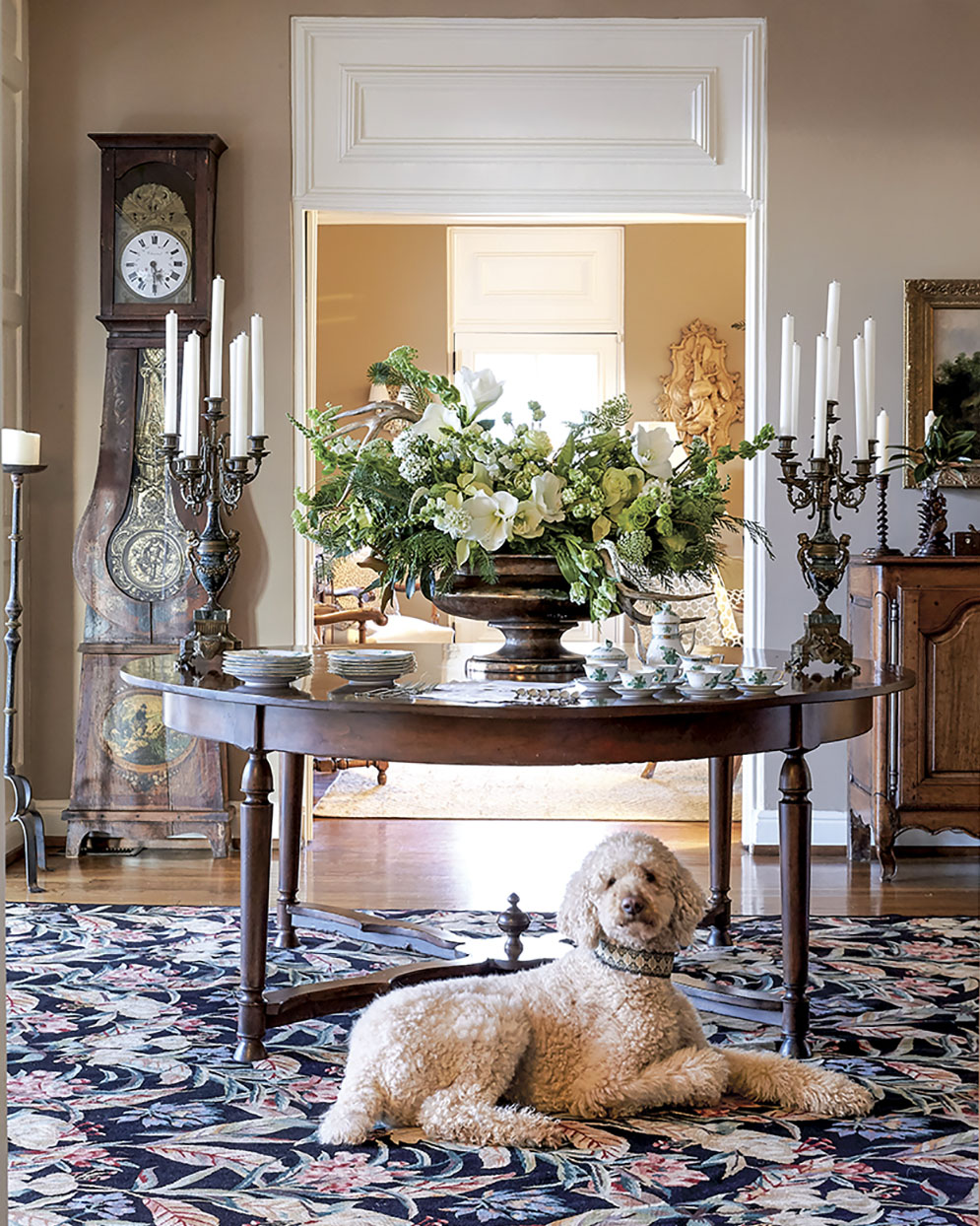 Grand green and white holiday floral design by Kakhi Huffaker Wakefield of K Wakefield Designs, placed on a round entry table in an elegantly styled foyer. A dog lies beneath the table